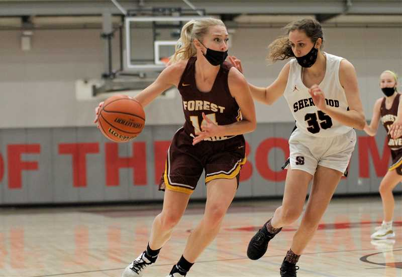 PMG PHOTO: WADE EVANSON - Forest Grove's Ally Hammond attacks Sherwood defender Sophia Carleton during the Vikings' game with the Bowmen Tuesday, June 15, at Sherwood High School.
