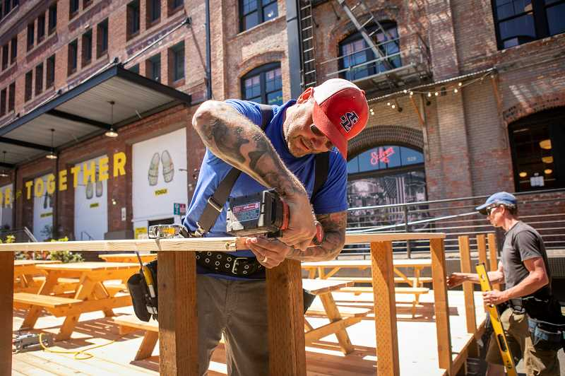 PMG: JAIME VADEZ - Robert Cote of Cote Construction building a deck in the right of way on Northwest 13th Avenue for the River Pig Saloon. He was told it might stay for three years.
