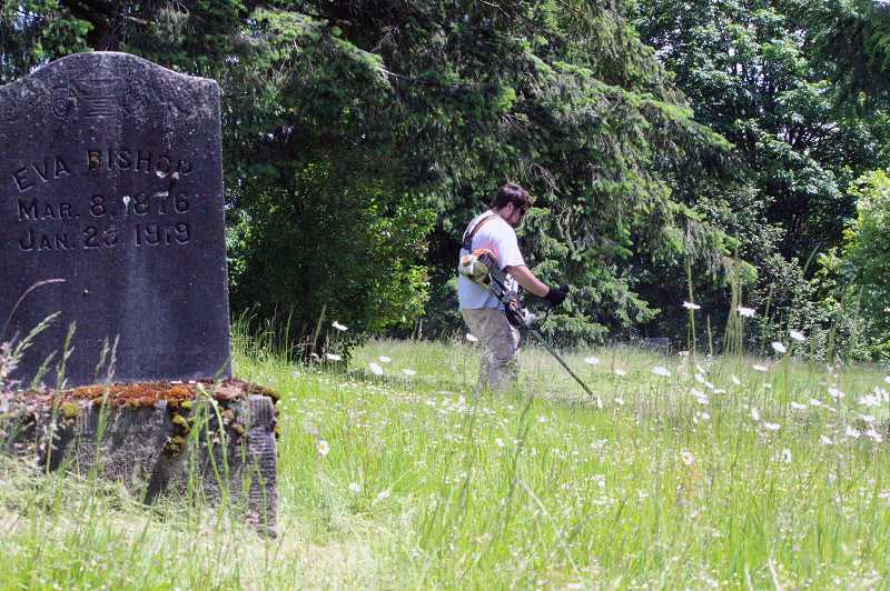COURTESY PHOTO: COLUMBIA COUNTY - Work crew volunteer Ross Clark cuts grass beyond a gravestone for a woman who died in 1919.