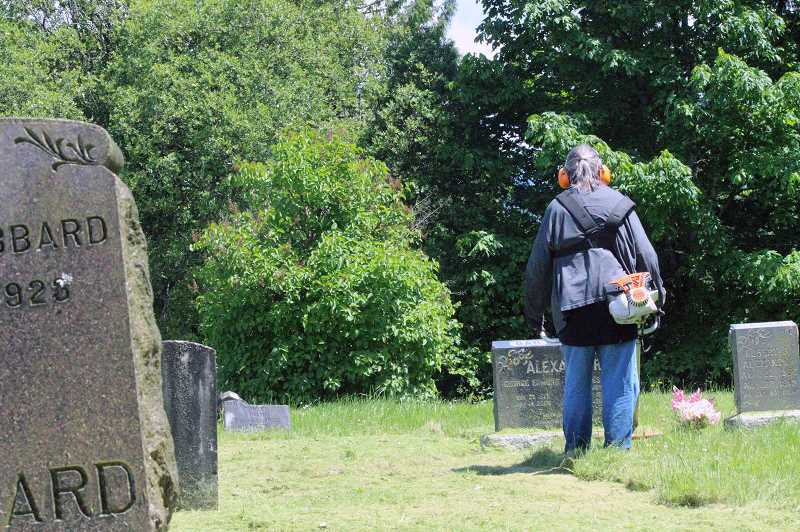 COURTESY PHOTO: COLUMBIA COUNTY - A work crew member clears debris from around gravestones.