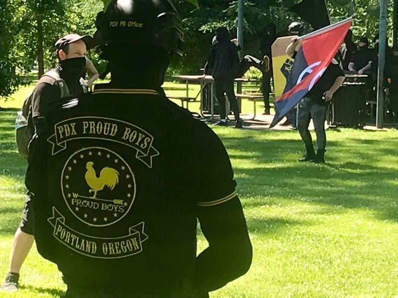 PMG PHOTO: ZANE SPARLING - A man wears the uniform of the Portland Proud Boys while facing off with local antifa demonstrators in Clackamette Park in Oregon City.