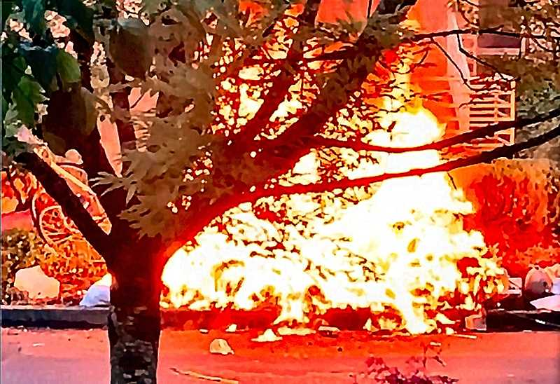 CONTRIBUTED PHOTO - An explosion followed by a huge fire erupted at a tent inhabited by a homeless person behind the Woodstock Bi-Mart store awakened neighbors at dawn on June 15th and made ashes of the tent and surrounding belongings and trash. The store itself was not damaged.
