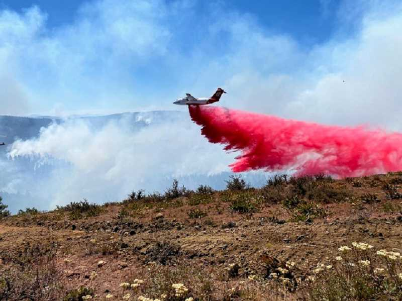 PHOTO BY SHAWN JACA - Looking south off of Foreman Point, an air tanker drops retardant on the S-503 Fire on the north part of the Warm Springs Reservation.