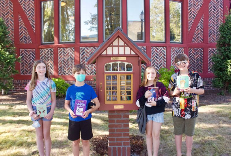 PMG PHOTO: CHRISTOPHER KEIZUR - Cailin Weisend, Elliot Stephens, Bella Schroeder and Luke Bemis all came together to find books to fill the Little Library.