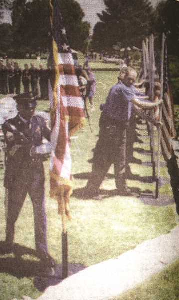 CENTRAL OREGONIAN - 1st Sgt. Shipley places the American flag first, followed by the 1996 Prineville Hot Shots crew. The flags were a reminder of the Prineville 14, lost at Glenwood Springs, Colorado, in 1994.