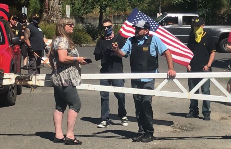 PMG PHOTO: ZANE SPARLING - Members of the Portland Proud Boys spoke with a Clackamette Park caretaker, left, during a confrontation with antifa members during an event that was later declared a riot by Oregon City Police on June 18.