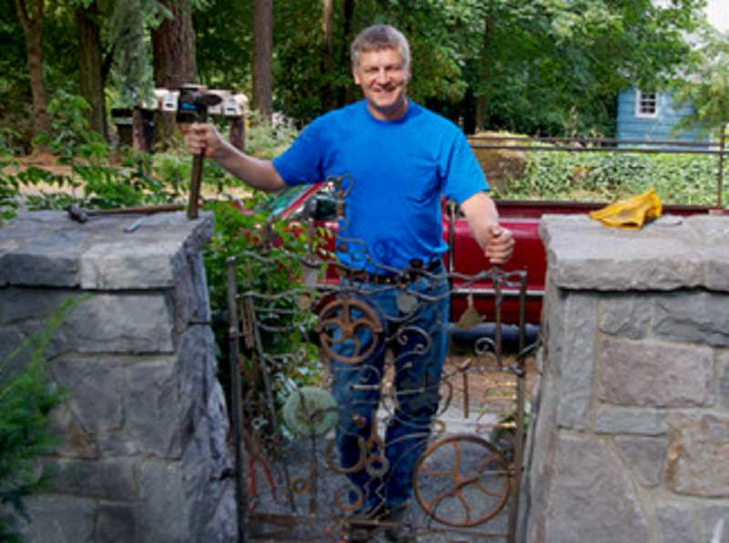 COURTESY PHOTO - Well-known Oregon metal sculptor Ray Huston installs the gate he designed and fabricated in 2012.