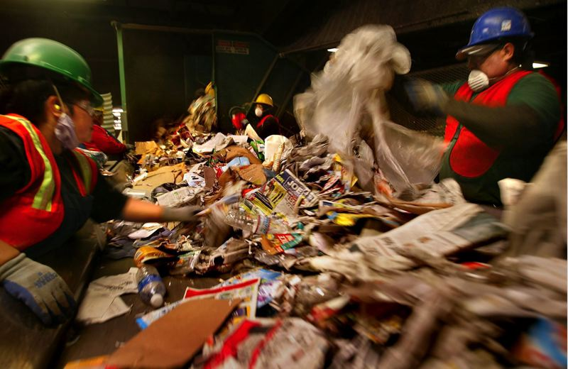 FILE PHOTO - Workers at Far West Fibers do the initial sort of co-mingled recycled products in 2008.
