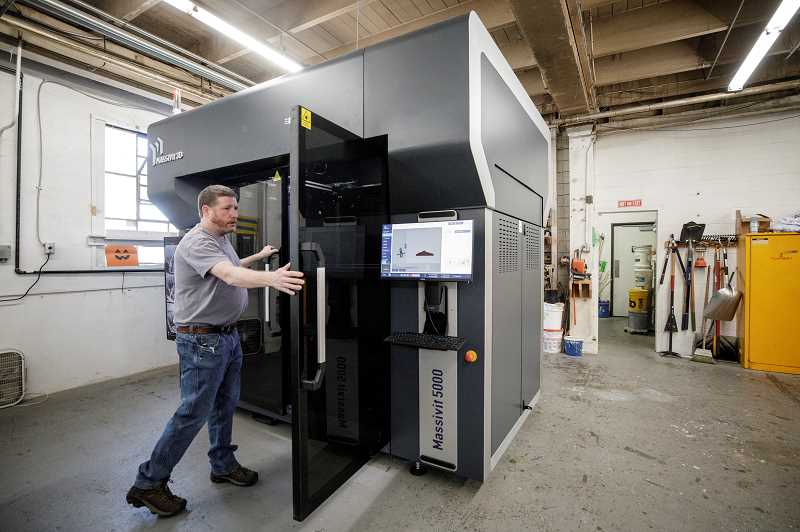 PAMPLIN MEDIA GROUP: JONATHAN HOUSE  - Technical designer Tyler Smith who works at Figure Plant in North Portland, with the $500,000 large format 3D printer the company acquired in May. Smith says it will make outputting one-off objects with organic forms much quicker than carving them from Styrofoam or plywood. The gel comes in five gallon buckets, seen here at rear.