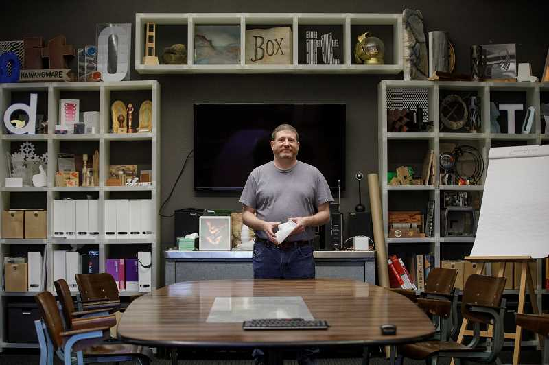 PAMPLIN MEDIA GROUP: JONATHAN HOUSE  - Technical Designer Tyler Smith at Figure Plant's office in Kenton, North Portland, surrounded by some of the promotional objects the company has made.