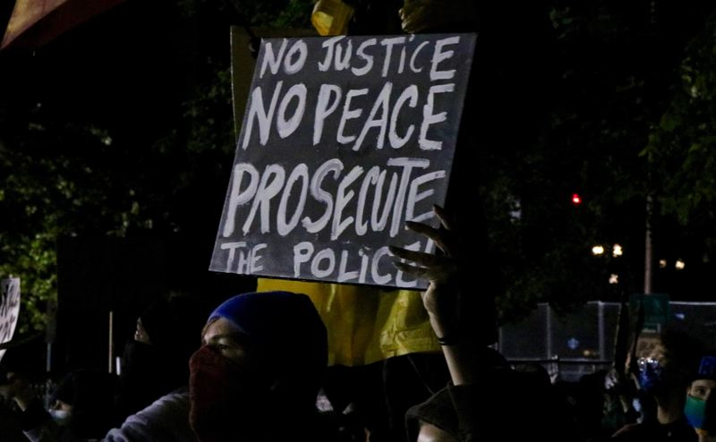 PMG PHOTO: ZANE SPARLING - A protester holds a sign calling for the prosecution of police officers during a demonstration in downtown Portland last year.