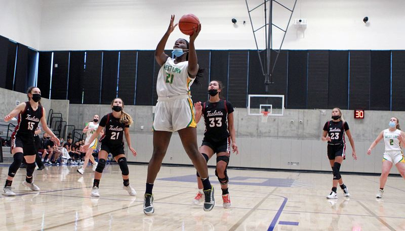 PMG PHOTO: MILES VANCE - West Linn senior Aaronette Vonleh goes up to score during her team's 65-27 win over Tualatin at Grant High School in the third-place game of the Maroon bracket of the culminating week tournaments on Thursday, June 24.