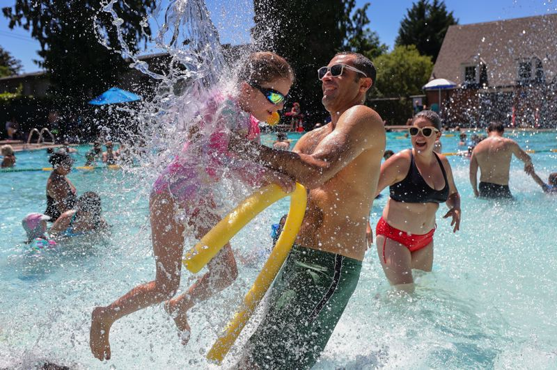 PMG PHOTO: JONATHAN VILLAGOMEZ - Families frolic in the Sellwood Pool in Portland on Friday, June 25.