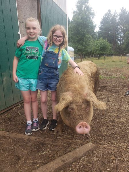 COURTESY PHOTO - River Mill Elementary School students Shelby Munds and Aliana Huff are all smiles with Skipper, one of the residents of Out to Pasture Animal Sanctuary. Munds and Huff raised $1230.10 for the sanctuary.