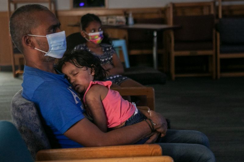 PMG PHOTO: JAIME VALDEZ - Raj Nuvvula holds his youngest daughter, Shravya, 2, as they watch Frozen II with his oldest daughter, Bravya, 9-1/2, while cooling off from the hot temperatures at the Wilsonville Library.