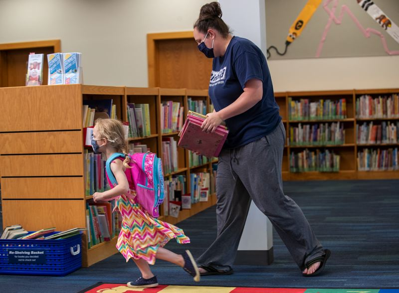PMG PHOTO: JAIME VALDEZ - Layne Harmon, 4, leads her mother, Amanda, out the children's section from the Wilsonville Library. The Harmons took advantage of the air conditioning at the library during the hot heat in the metro area.