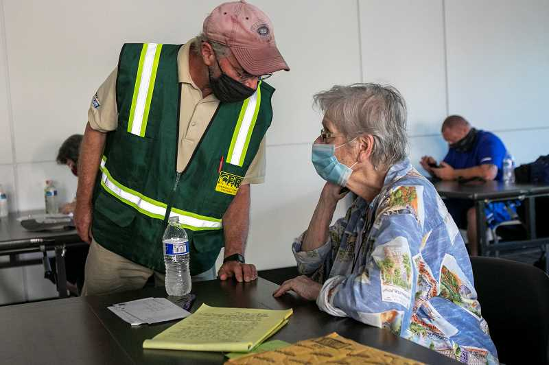 PMG PHOTO: JAIME VALDEZ - Tigard CERT member Fred Field-Eaton asks Nancy Budrow if she needs more water while she uses the cooling center at Tigard City Hall on Monday.