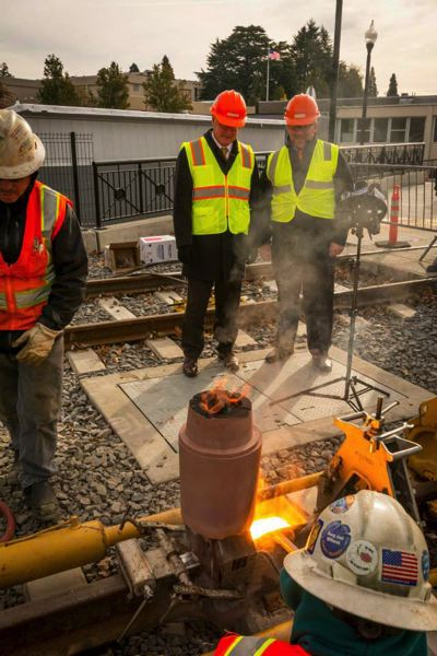 PHOTO COURTESY: TRIMET - TriMet's then-General Manager Neil McFarlane and Milwaukie Mayor Jeremy Ferguson watch a construction crew complete the final weld for Milwaukie light rail IN 2014. Three regional lawmakers are urging Congress to pass green transportation measures.