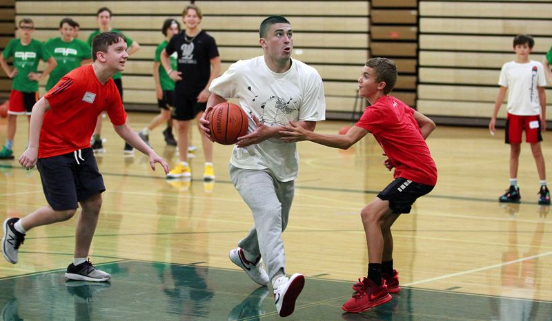 PMG PHOTO: MILES VANCE - Former West Linn great and Boston Celtics guard Payton Pritchard (center) came home to help lead the 2021 Payton Pritchard Basketball Camp at West Linn High School from June 29-July 2.
