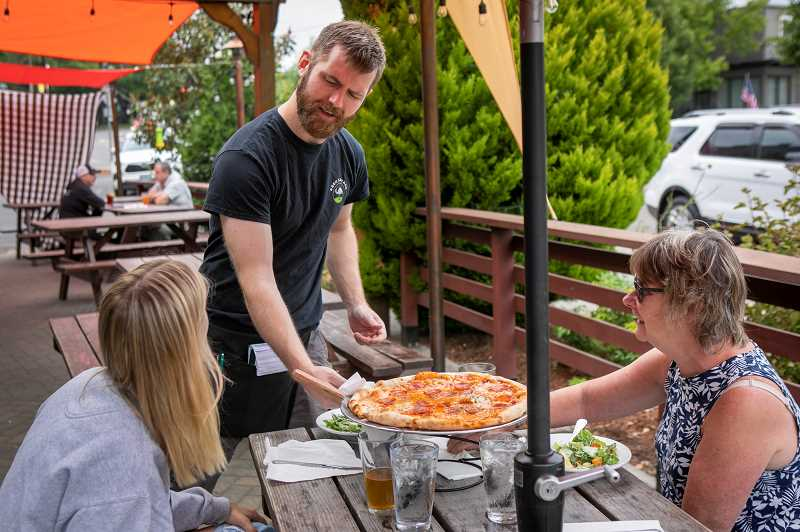 PMG PHOTO: JAIME VALDEZ - Chris Hreha, a server at Cooper Mountain Ale Works, serves a pizza to Sarah Bergstrom, left, and her mom, Ann, on the first day of no mask requirement on Wednesday, June 30. That same day marked two weeks that Hreha was fully vaccinated.