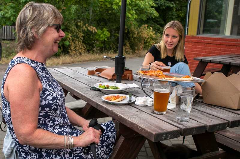 PMG PHOTO: JAIME VALDEZ - Sarah Bergstrom, left, and her mom, Ann, enjoy a pizza at Cooper Mountain Ale Works on the first day of no mask requirement on Wednesday, June 30.