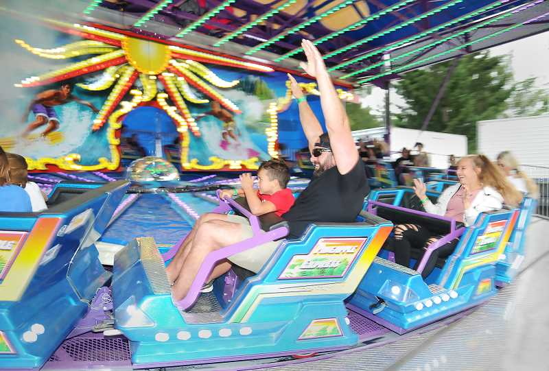 PMG PHOTO: GARY ALLEN - Kids and kids at heart enjoy the rides in the carnival midway on Wednesday evening.