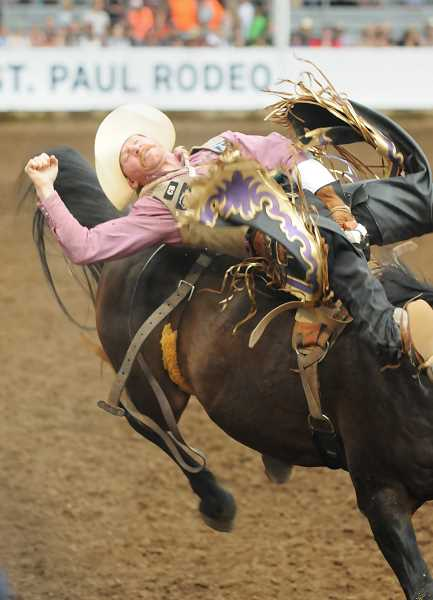 PMG PHOTO: GARY ALLEN - A saddle bronc rider employs his best technique in order to earn points and possible purse winnings on Wednesday evening.