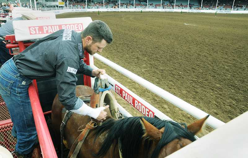 PMG PHOTO: GARY ALLEN - A competitor prepares for the saddle bronc competition on Wednesday evening.