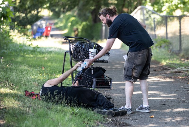 MULTNOMAH COUNTY PHOTO: MOTOYA NAKAMURA - A Cascadia volunteer delivers a water bottle to a homless person lying in the grass during the unprecedented June heat wave.