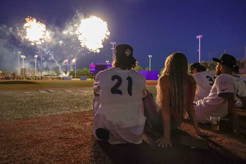PMG PHOTO: JONATHAN VILLAGOMEZ - Hillsboro's Blaze Alexander takes in the fireworks with teammates and friends following the Hops' win over the Emeralds Sunday night, July 4, at Ron Tonkin Field.