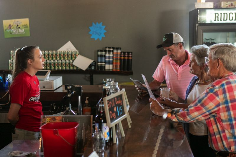 PMG PHOTO: JAIME VALDEZ - Olivia Kimmel, a bartender at Ridgewalker Brewing Company, helps customers in the lunch hour Friday, July 2.