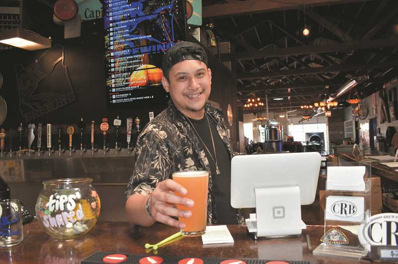 RAMONA MCCALLISTER - Jeromy Pauls, who has worked for CR Brewing for approximately three years, serves up a Heavy Blonde Sour, which is served on tap and made locally at their brewery.