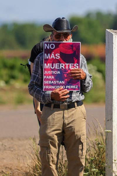 PMG PHOTO: JONATHAN VILLAGOMEZ - A man holds up a sign decrying the death of Sebastian Francisco Perez, a farmworker who died in the fields during a record-shattering heat wave last month.