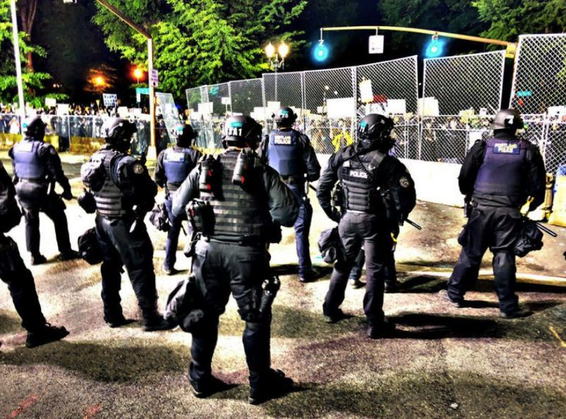 POOL PHOTO VIA OPB - Portland Police Bureau officers stood guard as demonstrators massed along fencing surrounding the Multnomah County Justice Center on June 6, 2020.