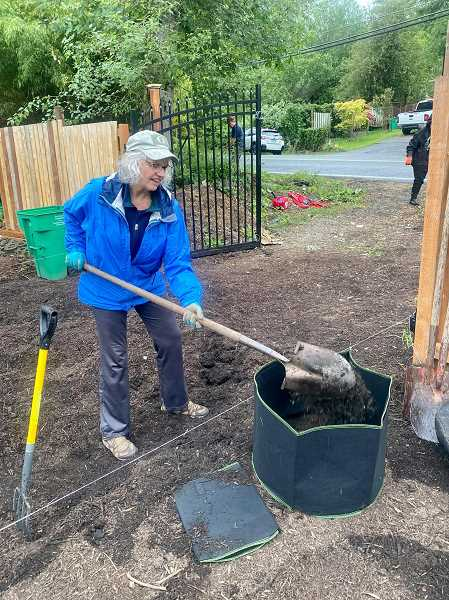 PHOTO COURTESY: WINDERMERE REAL ESTATE - Deanna Wilson, a broker with the Raleigh Hills office of Windermere Real Estate, lends a hand at the Focus on Youth Sunflower Farm on Southwest Garden Home Road. Wilson was among several Windermere agents who volunteered with local organizations to mark the firms 37th annual community service day.
