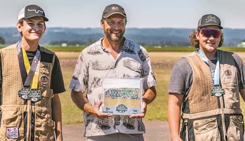 COURTESY PHOTO: DAVID CRAIG - Competitors David Goehner (left) and Wyatt Land flank coach David Craig after the Tigers took first place at the state high school clay target tournament in June.