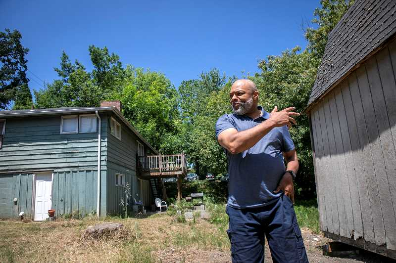 PMG PHOTO: JAIME VALDEZ - Vernon Baker, executive director of Just Compassion, points to an old outbuilding that will be removed when the organization builds a new shelter/transitional housing facility after razing the home at left.