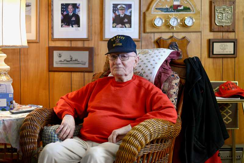 PMG PHOTO: ANNA DEL SAVIO - Frank Weber sits at his home in Scappoose. On the wall behind him, Weber has collected photos of past Chiefs of Naval Operations, who head the Navy.