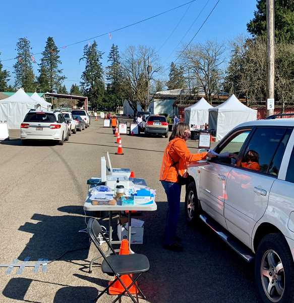 COURTESY PHOTO: KIMBERLY JACOBSEN/OSU EXTENSION - Jan Williams, with the OSU Extension Service in Clackamas County, collects paperwork from participants before they receive their shot at the drive-thru COVID-19 vaccination clinic this spring.