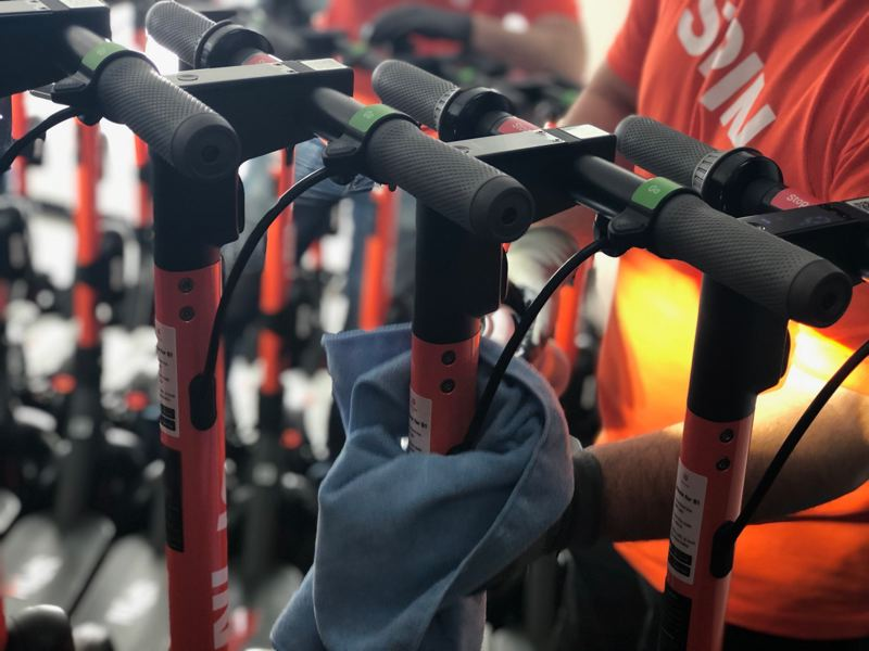 FILE - A Spin employee disinfects a row of scooters owned by the ride share company in 2020.