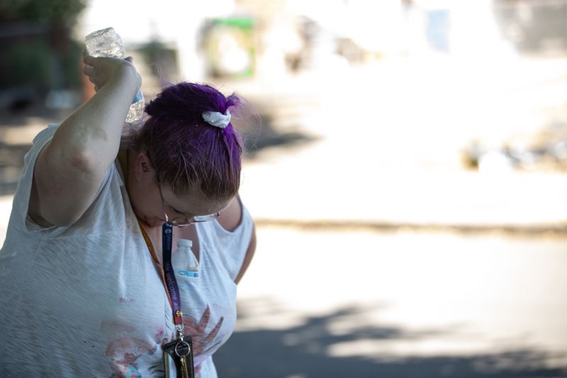 PMG FILE PHOTO - A woman pours a water bottle onto her neck during the deadly June heat wave.