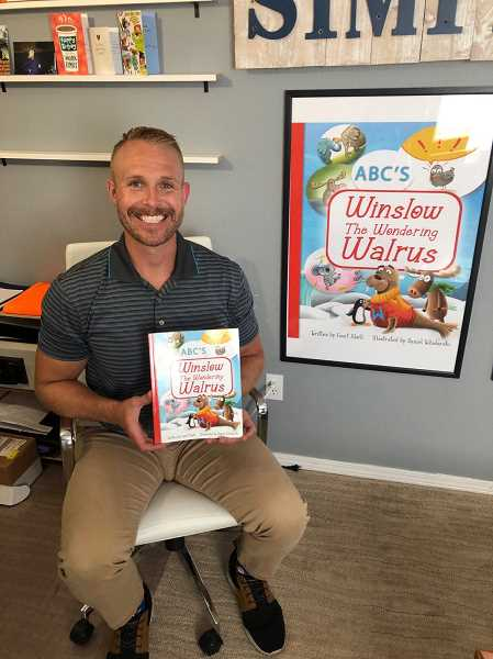 """RAMONA MCCALLISTER - Court Abell proudly displays his children's ABC book, """"Winslow the Wandering Walrus."""" Abell's book was inspired by his young sons. To his right is a poster he used to market the book."""