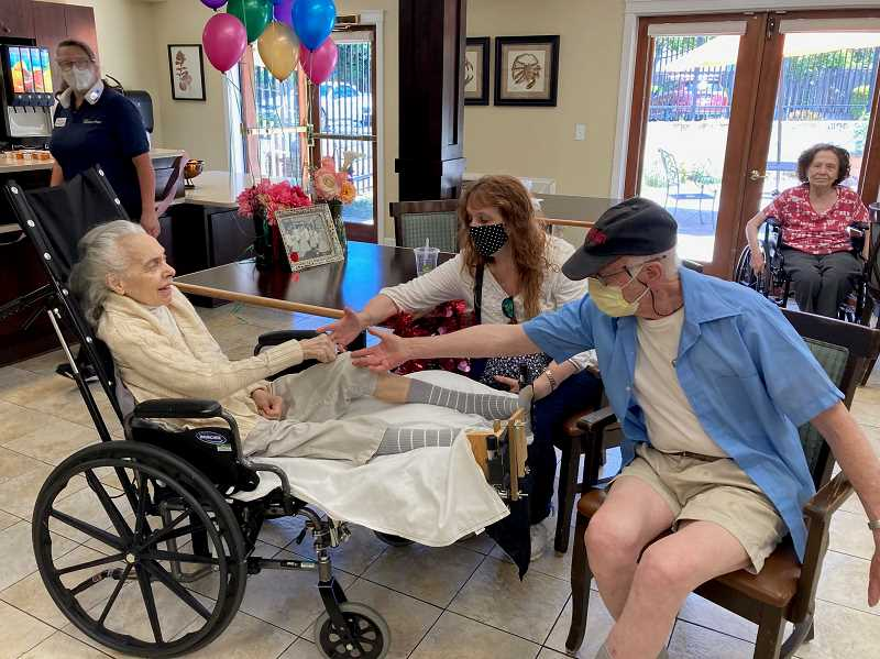 COURTESY PHOTO - Maria Herwig, left, holds hands with her daughter Angela and husband, Henry, as the couple celebrates their 62nd wedding anniversary at Royalton Place Assisted Living in Milwaukie.