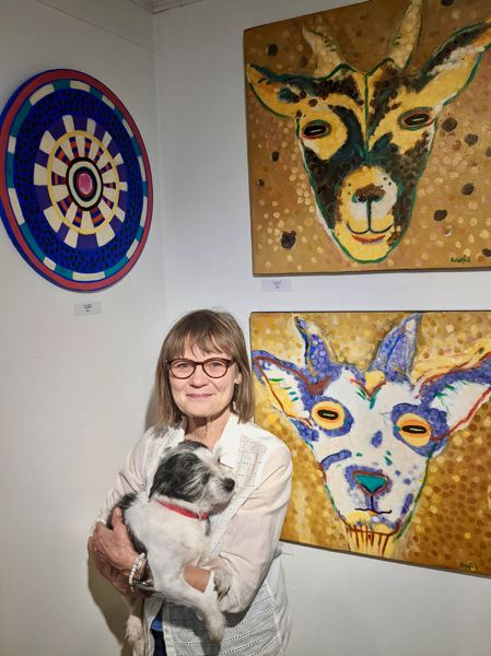 PMG PHOTO: EMILY LINDSTRAND - Nina Bradford and her dog, Bradford, stand alongside several pieces in her show 'Make Art Not War.'