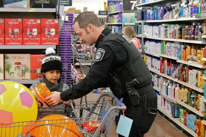 PHOTO COURTESY: CCPOBF - An officer helps a child shop at an SWAC event.