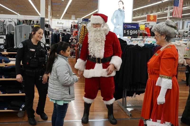 PHOTO COURTESY: CCPOBF - A child meets Mr. and Mrs. Claus while an officer watches happily.