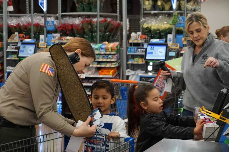 PHOTO COURTESY: CCPOBF - Officers help children check out their new items.