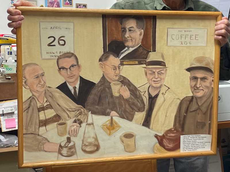 PMG PHOTO: ANNA DEL SAVIO - Cliff Bauer holds up a painting that shows him and friends at a restaurant they frequented years ago.