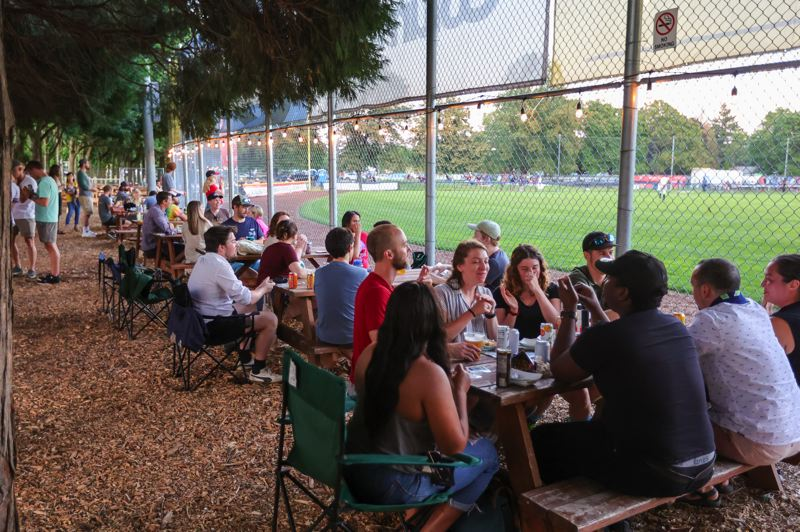 PMG PHOTO: JONATHAN VILLAGOMEZ - Fans enjoy a July 13, 2021, Portland Pickles game from new picnic tables behind the outfield fence. The Pickles start their final nine-game home stand at Walker Stadium on July 24.
