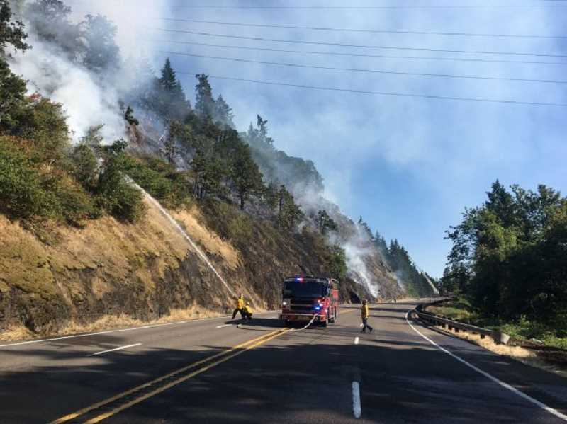 COURTESY PHOTO: CLACKAMAS FIRE - Firefighters battle a brush fire south of Oregon City on July 14.
